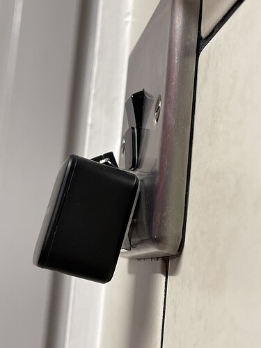 Black SwitchBot on a metal light switch, with a triangular binder clip forcing the SwitchBot to the correct angle.